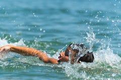 de jongenstiener zwemt in het overzees met grote plonsen Stock Afbeeldingen