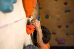 De jongenstreinen op een het beklimmen muur stock foto's