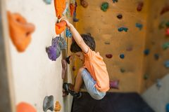 De jongenstreinen op een het beklimmen muur stock afbeeldingen
