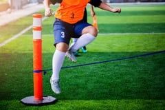 De jongensvoetballer voert coördinatie en sterkteboren door over kabel op groen kunstmatig gras uit te springen stock afbeeldingen