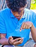 De jongenswerken met smartphone Royalty-vrije Stock Afbeelding
