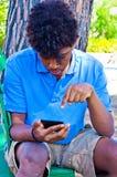 De jongenswerken met smartphone Stock Afbeelding
