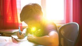 De jongenszitting bij schoolbank en doet het werk Schoolonderwijs De zon` s stralen door het glas stock video