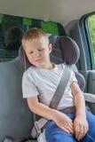De jongenszitting in een auto als veiligheidsvoorzitter maakt langs vast Royalty-vrije Stock Afbeelding