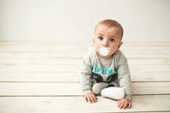 De jongenszitting van de één éénjarige leuke baby op houten vloer Stock Afbeeldingen