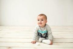 De jongenszitting van de één éénjarige leuke baby op houten vloer Royalty-vrije Stock Fotografie