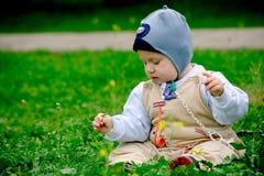De jongenszitting van de baby op gras Stock Afbeelding