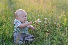 De jongenszitting van de gelukbaby op het gras op gebied Stock Foto's
