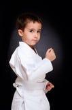 De jongenszitting van de karate in witte kimono stock afbeelding