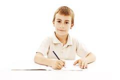 De jongenszitting van de school en het schrijven in notitieboekje royalty-vrije stock afbeeldingen