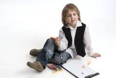 De jongenszitting van de tekening op een witte achtergrond. Stock Afbeelding