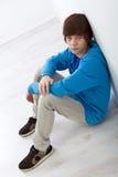 De jongenszitting van de tiener op de vloer door de muur Stock Fotografie