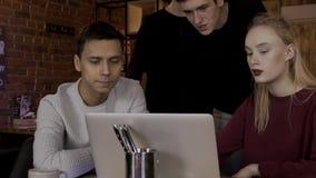 De jongeren bekijkt laptop in een koffie bij de lijst stock videobeelden