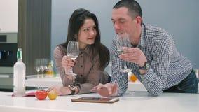 De jongeren die wijn drinken en gebruikt de lijst aangaande keuken stock videobeelden