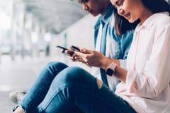 De jongeren gebruikt smartphone en glimlacht terwijl het zitten op vrije tijd Het concept van de technologie royalty-vrije stock afbeeldingen