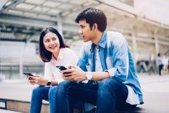 De jongeren gebruikt smartphone en glimlacht terwijl het zitten op vrije tijd stock afbeeldingen