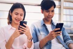 De jongeren gebruikt smartphone en glimlacht terwijl het zitten op vrije tijd royalty-vrije stock afbeeldingen