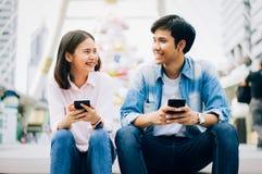 De jongeren gebruikt smartphone en glimlacht terwijl het zitten op vrije tijd stock afbeelding