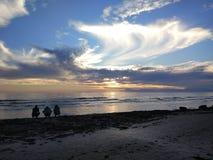 De jongeren geniet van de zonsondergang op het strand stock foto's