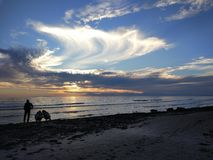 De jongeren geniet van de zonsondergang op het strand royalty-vrije stock foto's