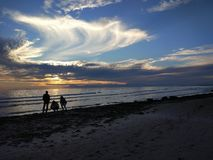 De jongeren geniet van de zonsondergang op het strand royalty-vrije stock afbeelding