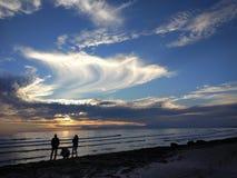 De jongeren geniet van de zonsondergang op het strand stock foto