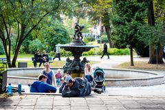 De jongeren in het stadspark ontspant, luistert aan muziek en zingt stock afbeelding