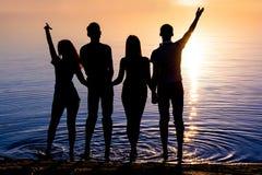 De jongeren, kerels en meisjes, bevindt zich op het strand en watc Royalty-vrije Stock Afbeeldingen