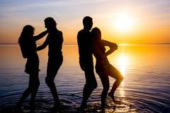 De jongeren, kerels en meisjes, danst op het strand bij zonsondergang Royalty-vrije Stock Foto