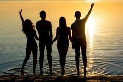 De jongeren, de kerels en de meisjes, studenten bevindt zich op het strand Stock Fotografie