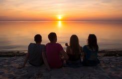 De jongeren - kerels en meisjes - zit op het strand en let op s Royalty-vrije Stock Fotografie