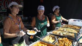 De jongeren kookt snel Aziatisch voedsel op de straat stock video