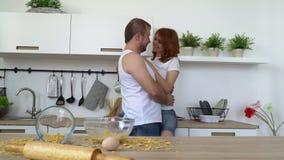 De jongeren omhelst in keuken stock footage