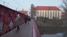 De jongeren op het rood overbrugt het leiden tot Ostrow Tumski in Polen stock video