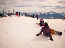 De jongeren op snowboard rust alvorens om weg te gaan te skien stock afbeeldingen