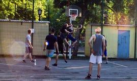 De jongeren speelt Straatbasketbal stock foto's