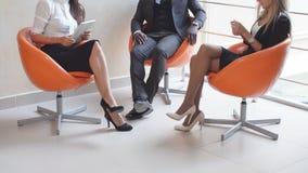 De jongeren verwacht gesprekken zittend op stoelen in een bureaugebouw het gesprek voor de baan royalty-vrije stock foto