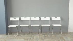 De jongeren verwacht gesprekken zittend op stoelen in een bureaugebouw het gesprek voor de baan de rekruten zijn bored stock foto