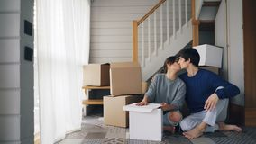 De de jongerenechtgenoot en vrouw spreken en kussen zitting op vloer van nieuw huis dichtbij trap en dromen het maken stock footage