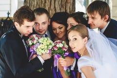 De jonggehuwden bevinden zich rond samen met hun vrienden tijdens een gang Stock Foto