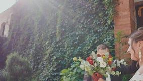 De jonggehuwden dansen joyously bij de bakstenen muur met het kweken van takken van druiven De bruidegom in de dans kust zijn bru stock videobeelden