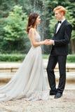De jonggehuwden houden handen en stock afbeelding