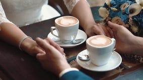 De jonggehuwden houden handen terwijl het zitten in een koffie, zittend bij een lijst waarop er twee mokken koffie, close-up zijn stock footage