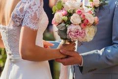 De jonggehuwden houden hans met bouquete Royalty-vrije Stock Afbeelding