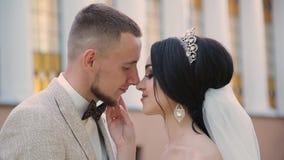 De jonggehuwden koesteren en genieten van elkaar op hun huwelijksdag stock videobeelden