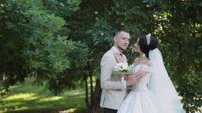 De jonggehuwden koesteren en genieten van elkaar op hun huwelijksdag stock video