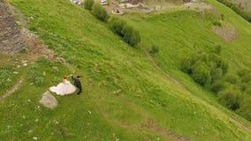 De jonggehuwden in liefde gaan onderaan een steile berg langs een smalle weg georgië Kazbegi stock video