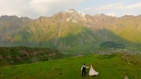 De jonggehuwden lopen in de avond in de weide tegen de achtergrond van mooie bergen Concept - de gehele wereld voor stock video