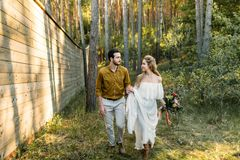 De jonggehuwden lopen bij het bosmeisje in witte kleding en de mens in een olijfoverhemd Rustiek huwelijk kunstwerk royalty-vrije stock foto