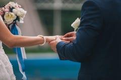 De jonggehuwden ruilen ringen, zet de bruidegom de ring op de bruid` s hand stock foto